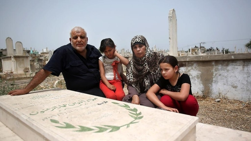 In this June 3, 2014 photo, Imad and Rawda Zanoun and their grandchildren Rawda and Farah visit the grave of the girls' father, Alaa Eldin, who was killed in a 2007 fight between Hamas and Fatah days before the Hamas take over in Gaza City. The Palestinian unity government has settling demands of justice for hundreds killed and wounded in fighting, that culminated in the 2007 Hamas takeover of the Gaza Strip, ahead of them. (AP Photo/Hatem Moussa)