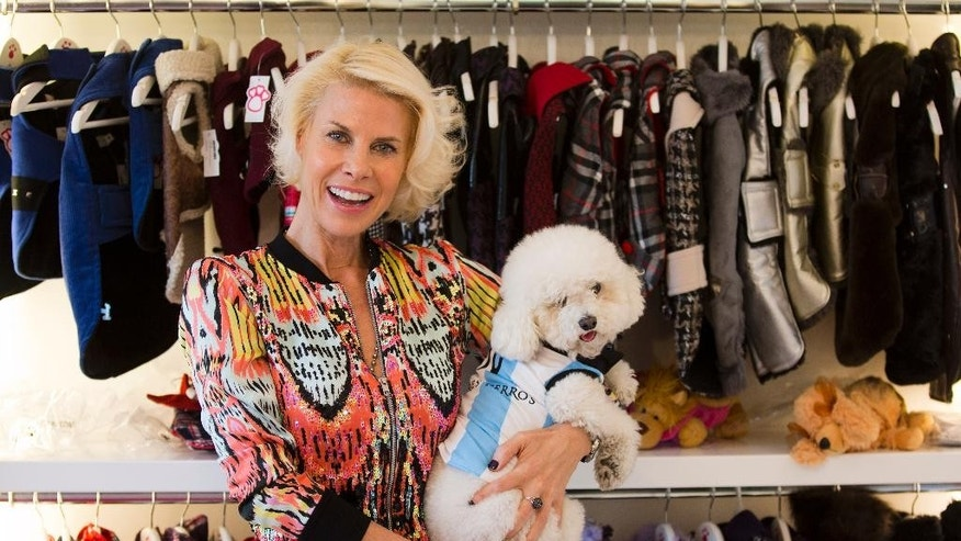 Karen Reichardt, owner of a pet store, poses with her dog wearing a garment resembling the jersey of the Argentine national soccer squad in Buenos Aires, Argentina, Thursday, June 5, 2014. Reichardt designed a number of garments for pets ahead of the World Cup that starts next week in Brazil. (AP Photo/Victor R. Caivano)