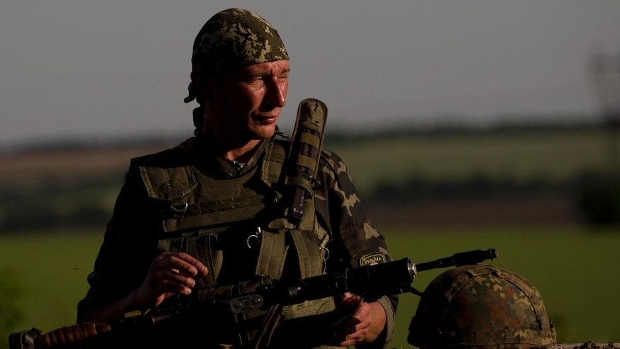 An Ukrainian soldier observes the road at a checkpoint outside the town of Amvrosiivka, eastern Ukraine, close to the Russian border, Thursday, June 5, 2014. The Ukrainian military was on alert on its eastern border with Russia on Thursday amid reports that separatist forces launched attacks on a border crossing near the village of Marinyvka.(AP Photo/Vadim Ghirda)