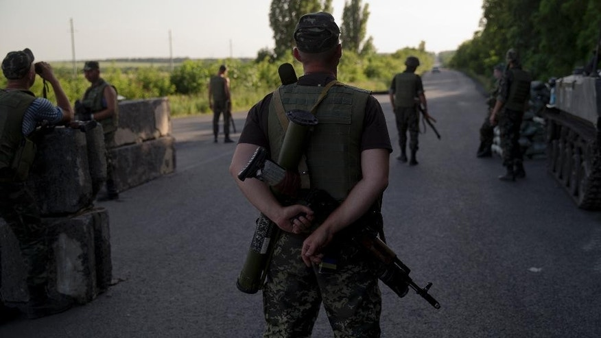 Ukrainian soldiers man a checkpoint outside the town of Amvrosiivka, eastern Ukraine, close to the Russian border, Thursday, June 5, 2014. The Ukrainian military was on alert on its eastern border with Russia on Thursday amid reports that separatist forces launched attacks on a border crossing near the village of Marinyvka.(AP Photo/Vadim Ghirda)