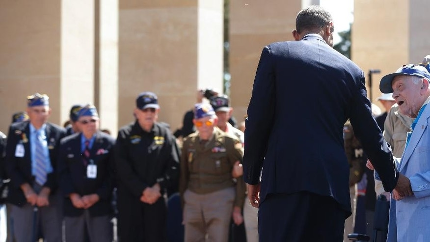 A veteran talks to U.S. President Barack Obama, at the Normandy American Cemetery, at Omaha Beach as he participates in the 70th anniversary of D-Day in Colleville sur Mer, Normandy, France, Friday, June 6, 2014. (AP Photo/Charles Dharapak)