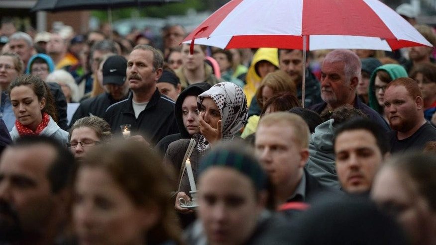 People take part in a candlelight vigil outside Royal Canadian Mounted Police headquarters in Moncton, New Brunswick, Canada on Friday, June 6, 2014. The RCMP say Justin Bourque, suspected in the shooting deaths of three Mounties and the wounding of two others in Moncton, was unarmed at the time of his arrest early Friday and was taken into custody without incident. (AP Photo/The Canadian Press, Sean Kilpatrick)