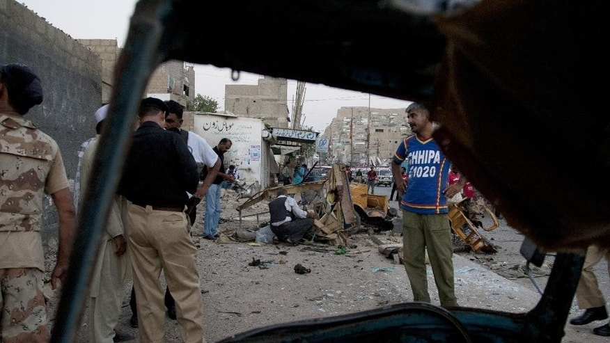 Pakistani security officials examine the site of a blast in Karachi, Pakistan, Thursday, June 5, 2014. Police and paramilitary officials cordon off the area after a bomb blast that left at least one dead and five injured, police said. (AP Photo/Shakil Adil)