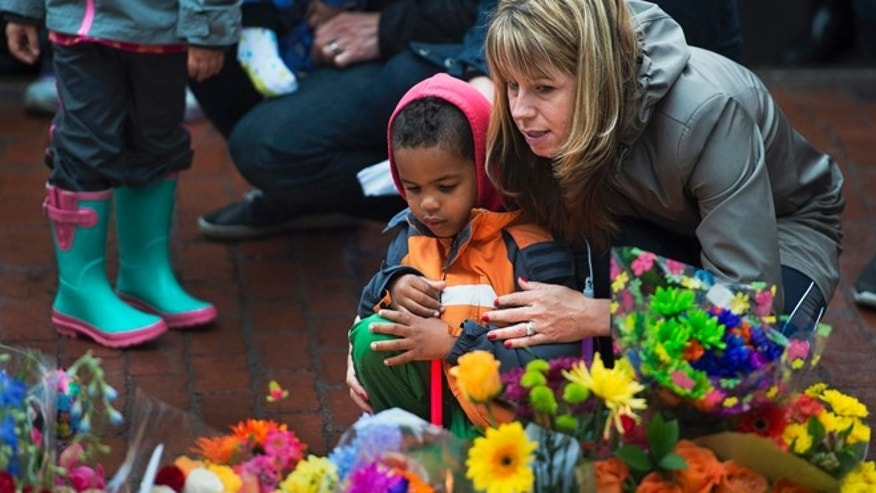 June 6, 2014: A woman and child participate in a candlelight vigil in Moncton, New Brunswick to pay respects to the three Royal Canadian Mounted Police officers who were killed and the two injured in shootings Wednesday.