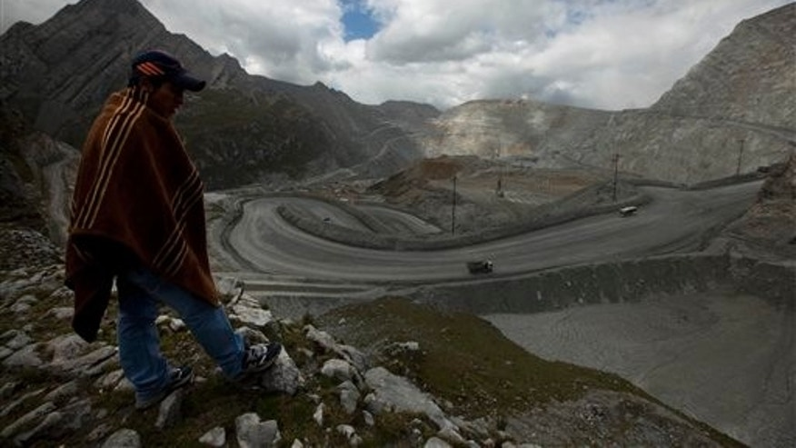 In this May 14, 2013 photo, sheep herder Mayqui Amado looks out at the open-pit Antamina mine in San Marcos, Peru, above property that is in dispute and from which the mine is trying to evict him and his cousins. Twenty years ago, this rugged, mineral-rich Andean nation bent over backward like no other country in the region to attract multinational mining companies, and became Latin Americas undisputed economic growth leader. (AP Photo/Martin Mejia)