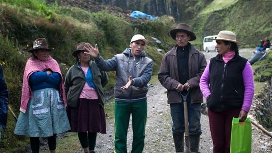 In this May 16, 2013 photo, farmer Enrique Chavez, center, complains about the adjacent Antamina mine as Virgilio Flores, second from right, and Lidia Zorilla look on in the village of San Antonio de Juprog, Peru. The women at left are not identified. Across Perus mine-pocked highlands, lax government regulation and frustration has led to a growing fury of protests. (AP Photo/Martin Mejia)
