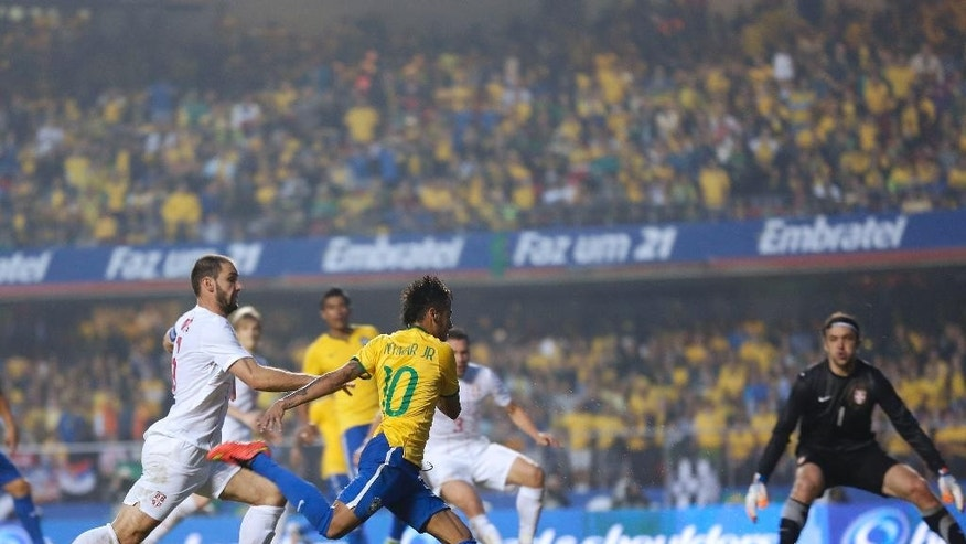Brazil's Neymar runs with the ball, as Serbia's Branislav Ivanovic challenges him during a friendly soccer match at the Morumbi stadium in Sao Paulo, Brazil, Friday, June 6, 2014. Brazil is hosting the World Cup soccer tournament that starts June 12. (AP Photo/Andre Penner)