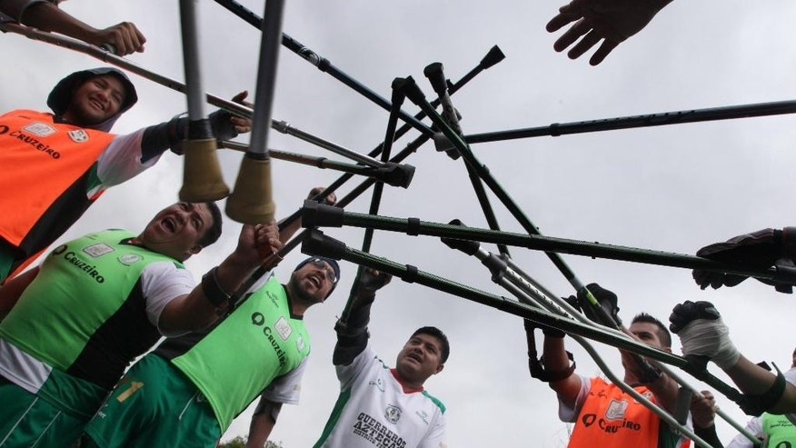 Players with amputated legs from the soccer team Guerreros Aztecas, or Aztec Warriors, join their canes together before playing a match with Los Dragones, or Dragons, in Mexico City, Saturday, June 7, 2014. Two World Cups of soccer will be held this year, and members of the Mexico City's Aztec Warriors are training tirelessly with the dream of playing in one of them. (AP Photo/Marco Ugarte)