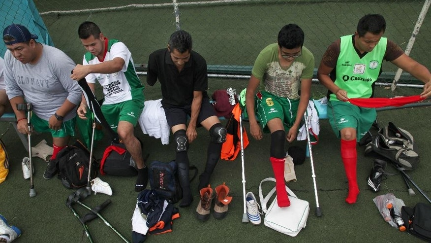 Players from the soccer team Guerreros Aztecas, or Aztec Warriors, who have amputated legs, get ready to play a match with Los Dragones, or the Dragons in Mexico City, Saturday, June 7, 2014. Sitting second from right is player Alejandro Balurch, 17, who had his leg amputated two years ago due to bone cancer. He practices as much as his chemotherapy will allow. (AP Photo/Marco Ugarte)