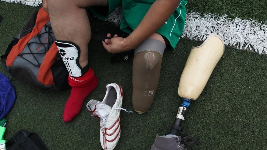 Osman Gonzalez takes off his prosthetic leg to play a soccer game with this team, Guerreros Aztecas, or Aztec Warriors, against Los Dragones, or the Dragons in Mexico City, Saturday, June 7, 2014. The team's goal is to reach the Amputee Soccer World Cup which will be held in Culiacan, Sinaloa from Nov. 30 to Dec. 8. Gonzalez, 31, said he lost his leg in an electrical accident when he was 23. (AP Photo/Marco Ugarte)
