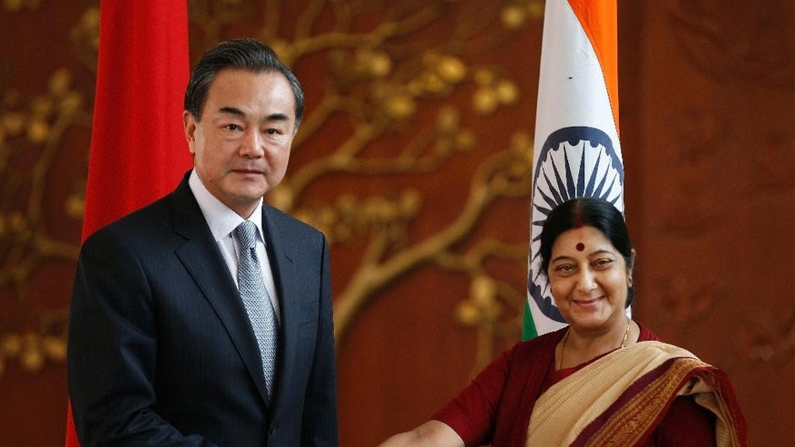 Indian External Affairs Minister Sushma Swaraj, right, shakes hands with her Chinese counterpart, Wang Yi, before their meeting in New Delhi, India, Sunday, June 8, 2014. Wang is here to meet Indian officials to push forward bilateral relations with the newly elected Narendra Modi led Indian government. (AP Photo/Saurabh Das)