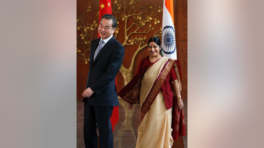 Indian External Affairs Minister Sushma Swaraj, right, and Chinese Foreign Minsiter Wang Yi laugh as they change sides to stand before the flags of their respective countries for a photo session before a meeting in New Delhi, India, Sunday, June 8, 2014. During his visit, Wang will meet Indian officials to push forward bilateral relations with the newly elected Narendra Modi led Indian government. (AP Photo/Saurabh Das)