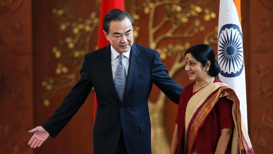 Indian External Affairs Minister Sushma Swaraj, right, and her Chinese counterpart, Wang Yi, leave for a meeting after a photo session in New Delhi, India, Sunday, June 8, 2014. Wang is here to meet Indian officials to push forward bilateral relations with the newly elected Narendra Modi led Indian government. (AP Photo/Saurabh Das)