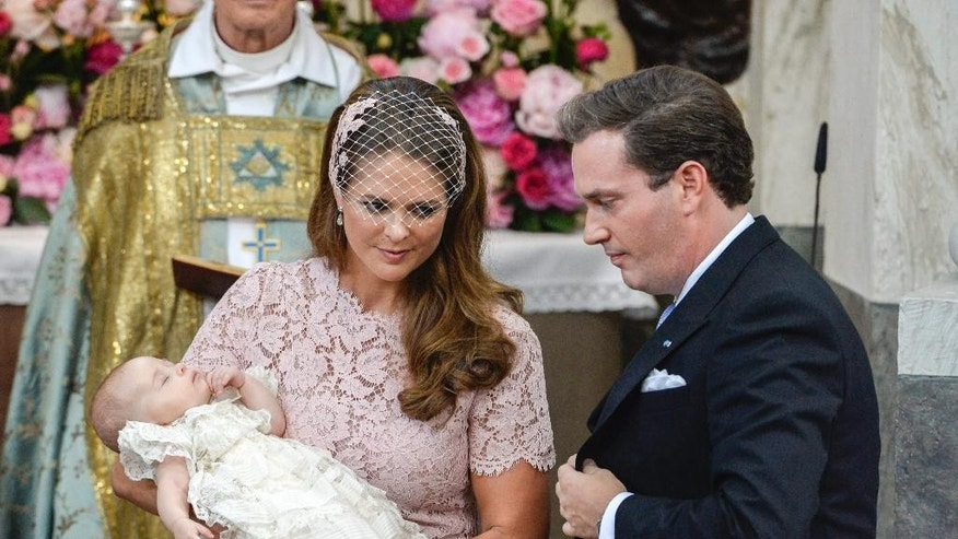 Princess Madeleine holds her daughter Princess Leonore watched by Christopher O'Neill, Princess Leonore's father, during the christening ceremony in the Drottningholm Palace church outside Stockholm, Sweden, Sunday, June 8, 2014. (AP Photo/TT, Jonas Ekstromer)   SWEDEN OUT