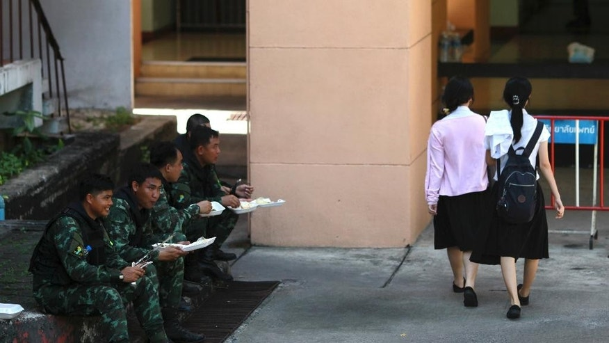 "Pedestrians walk past Thai soldiers eat lunch while guarding in Bangkok's Victory Monument, Thailand, Sunday, June 8, 2014. Thai police warned online critics of the military junta Friday that they will ""come get you"" for posting political views that could incite divisiveness, the latest reminder about surveillance of social media in post-coup Thailand. (AP Photo/Wason Wanichakorn)"