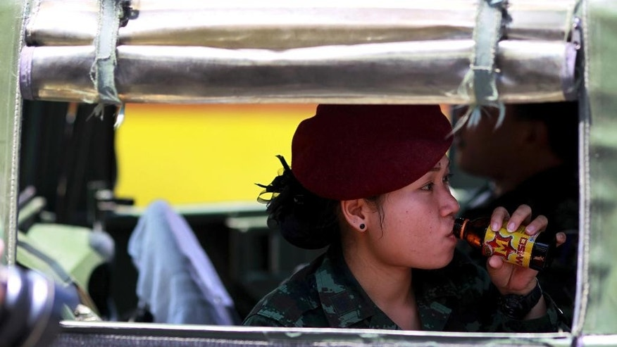 "A Thai soldier sips an energy drink while guarding inside a vehicle in Bangkok's Victory Monument, Thailand Sunday, June 8, 2014. Thai police warned online critics of the military junta Friday that they will ""come get you"" for posting political views that could incite divisiveness, the latest reminder about surveillance of social media in post-coup Thailand. (AP Photo/Wason Wanichakorn)"