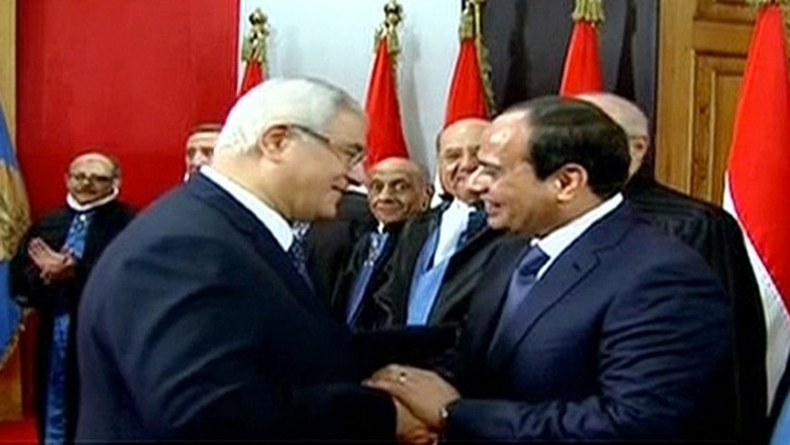 June 8, 2014: This image made from Egyptian State Television shows newly sworn in President Abdel-Fattah el-Sissi, right, being congratulated by outgoing interim President Adly Mansour, center left, after a ceremony at the Supreme Constitutional Court in Cairo, Egypt. (AP Photo/Egyptian State Television)
