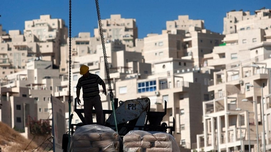 FILE - In this Nov. 2, 2011 file photo, a worker stands by construction materials to unload at a new housing unit in the east Jerusalem neighborhood of Har Homa. The collapse of Israeli-Palestinian peace talks has laid bare deep divisions in Prime Minister Benjamin Netanyahu's coalition that John Kerry's determined but ill-fated diplomacy had allowed to be papered over. Key coalition allies are demanding a government initiative to extract Israel from the West Bank, while others say now is the moment for enhanced Jewish settlement and even annexation of some areas. (AP Photo/Sebastian Scheiner, File)