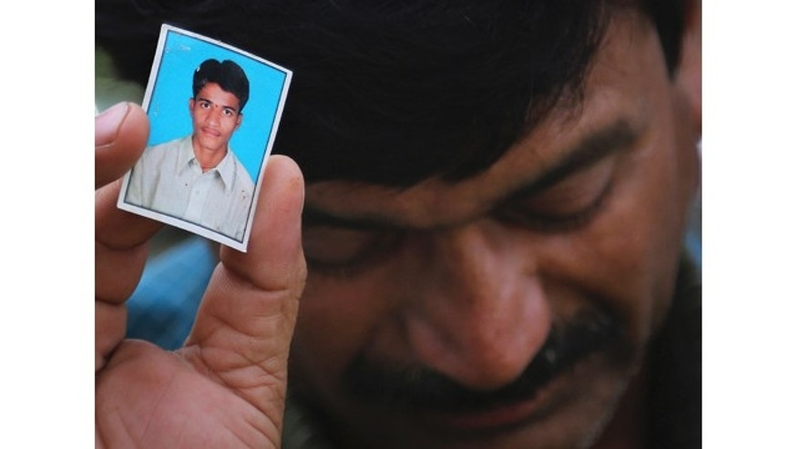 June 9, 2014: Bonath Shekar Naik shows a portrait of his son Rambabu, one of the 24 students feared dead during a field trip near the mountain resort town of Manali, at the college premises of VNR Vignana Jyothi Institute of Engineering and Technology, on the outskirts of Hyderabad, India. (AP Photo/ Mahesh Kumar A.)