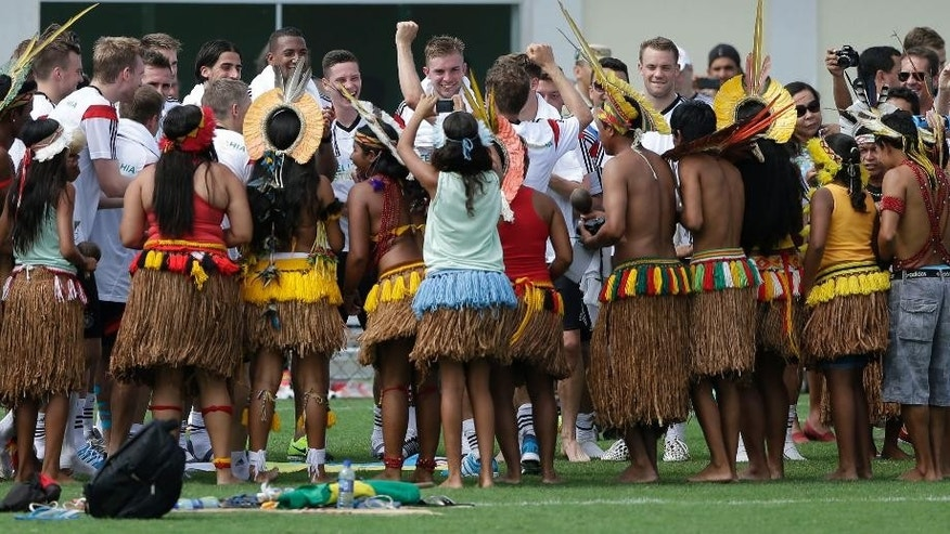 German's national soccer player Thomas Mueller, center, and his teammates visit with a group of Brazilian Indians who came to watch their training session, near Porto Seguro, Brazil, Monday, June 9, 2014. Germany will play in group G of Brazil's 2014 soccer World Cup. (AP Photo/Matthias Schrader)