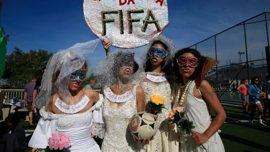 "Women wearing wedding dresses and vampire make up pose for a picture while holding a sign that reads in Portuguese, ""FIFA Gang"" during the final round of the 2014 People's Soccer Cup in Santo Cristo slum in Rio de Janeiro, Brazil, Sunday, June 8, 2014. The symbolic event wants to call attention to the illegalities and human rights violations occurring during the city's preparations for the World Cup and Olympics. The tournament is both a sporting event including games in men's and women's divisions and a political and cultural event. (AP Photo/Hassan Ammar)"