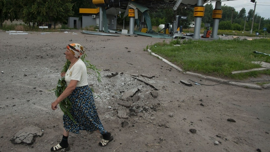June 9, 2014 - A woman walks past a gas station damaged by a mortar attack by Ukrainian government troops in Slovyansk, eastern Ukraine. Several buildings have been damaged by shelling in an eastern Ukraine city controlled by pro-Russian separatists, as the country's president announced that negotiations are underway to bring the conflict to an end.
