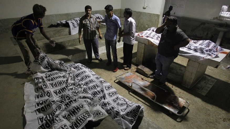 Volunteers look at dead bodies of people killed during an attack by unknown gunmen on Jinnah International Airport, Sunday night, June 8, 2014, in Karachi, Pakistan. Gunmen disguised as police guards stormed an airport terminal used for VIPs and cargo in Pakistan's largest city Sunday night, killing at least nine people as explosions echoed into the night, officials said.  (AP Photo/Fareed Khan)