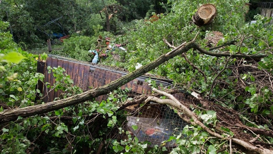 A destroyed  garden  house is covered with broken branches of trees  in a garden in Duesseldorf , western Germany, Tuesday June 10, 2014.  Authorities say at least six people were killed in western Germany as heavy rains, hail and high winds battered the region. In the North Rhine-Westphalia capital of Duesseldorf, police said two men and a woman who had sought refuge in the  garden house were killed late Monday when a large tree fell on the building, the dpa news agency reported Tuesday. Firefighters were able to rescue six others, and rushed them to hospitals for treatment. Many flights from Duesseldorf airport were delayed and some train routes were still closed Tuesday.  (AP Photo/dpa. Rolf Vennenbernd)