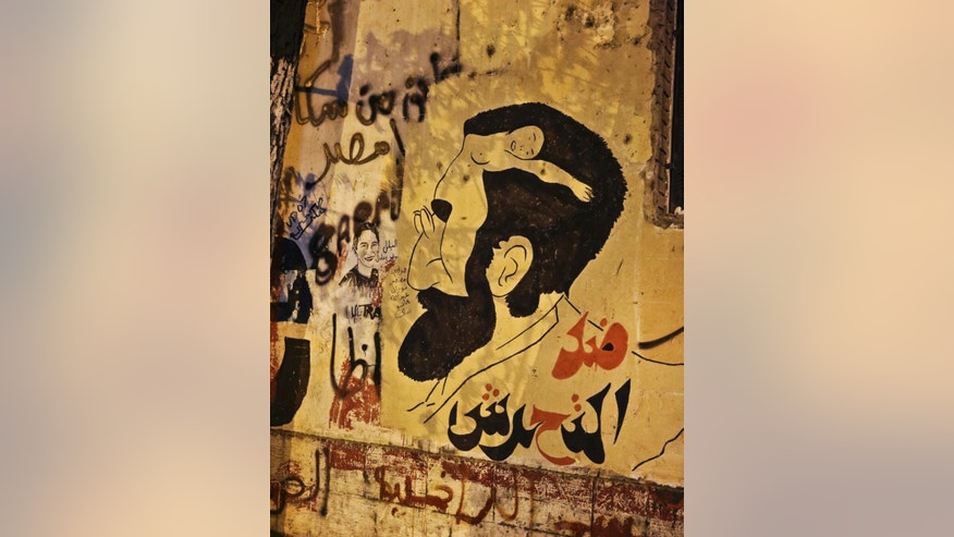 "In this Sunday, June 8, 2014 photo, anti-sexual harassment graffiti has been painted on a wall near Tahrir Square, Cairo, Egypt. Egyptian police on Monday arrested seven men for sexually assaulting a 19-year-old student during celebrations marking the inauguration of the country's new president in Cairo's central Tahrir Square the day before, security officials said. Sexual harassment has been one of Egypt enduring social ills, prompting authorities last week to issue a decree declaring it a crime punishable by up to five years in prison. Arabic reads, ""against harassment."" (AP Photo/Thomas Hartwell)"