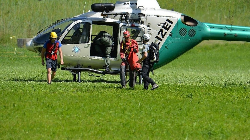 Members of the mountain rescue service  leave a police helicopter in Markt Schellenberg near Berchtesgaden, southern Germany, Monday June 9, 2014. Rescuers were working Monday to recover a man stuck deep inside a cave in the German Alps after he was injured by falling rocks Sunday an effort that police said could take days as experts negotiate a tricky labyrinth of vertical shafts and bottlenecks. A four-member rescue team reached the 52-year-old German cave researcher early Monday inside the Riesending cave system, near Berchtesgaden in Germany's southeastern corner, police said.( AP Photo/ Kerstin Joensson)