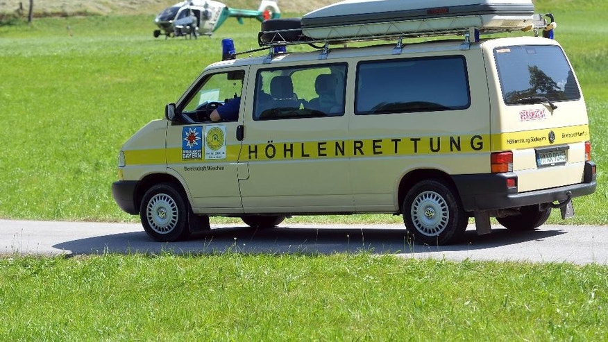 A car of the Bavarian cave rescue  service stands in front of a police helicopter  in Markt Schellenberg near Berchtesgaden, southern Germany, Monday June 9, 2014. Rescuers were working Monday to recover a man stuck deep inside a cave in the German Alps after he was injured by falling rocks Sunday an effort that police said could take days as experts negotiate a tricky labyrinth of vertical shafts and bottlenecks. A four-member rescue team reached the 52-year-old German cave researcher early Monday inside the Riesending cave system, near Berchtesgaden in Germany's southeastern corner, police said.( AP Photo/ Kerstin Joensson)