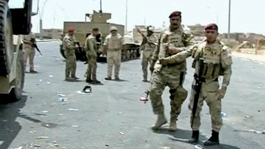 June 9, 2014: In this image taken from video obtained from the Iraqi Military, which has been authenticated based on its contents and other AP reporting, armed Iraqi soldiers take their positions during clashes with militants in Mosul, Iraq. (AP/Iraqi Military)