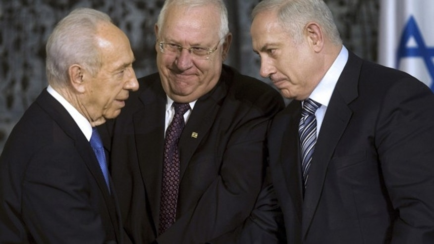 In this April 1, 2009, file photo, Israeli President Shimon Peres, left, greets Israeli Prime Minister Benjamin Netanyahu, right, as Knesset speaker Reuven Rivlin stands near during a handover ceremony at Peres' residence in Jerusalem. (AP)