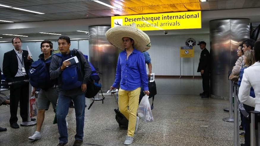 In this June 5, 2014 photo, foreigners arrive at the Guarulhos International Airport, in Sao Paulo, Brazil. With the World Cup set to open June 12, airports are bracing to welcome the crush of international travelers flying in for soccer's premier event. Brazilian authorities insist they're ready, but passengers may find themselves in for a rough landing. (AP Photo/Andre Penner)