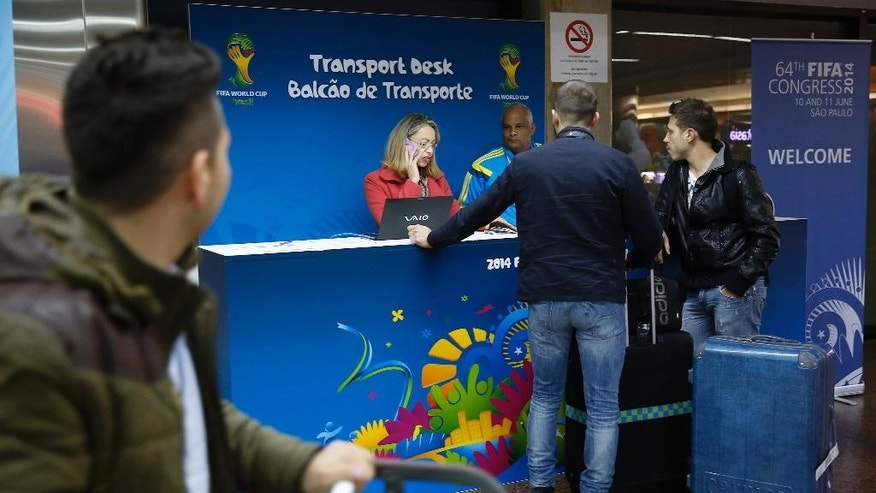 In this June 5, 2014 photo, FIFA volunteers help arriving passengers at the Guarulhos International Airport, in Sao Paulo, Brazil. Travelers who are used to stress-free arrivals, featuring clear signs in a language they understand are muddling their way through a troublesome task at Brazilian airports. For most travel in Brazil, flying is the only practical choice. The country is the size of a continent and there are no passenger rail connections, not even for the 260-mile stretch between its two largest cities, Rio de Janeiro and Sao Paulo. (AP Photo/Andre Penner)