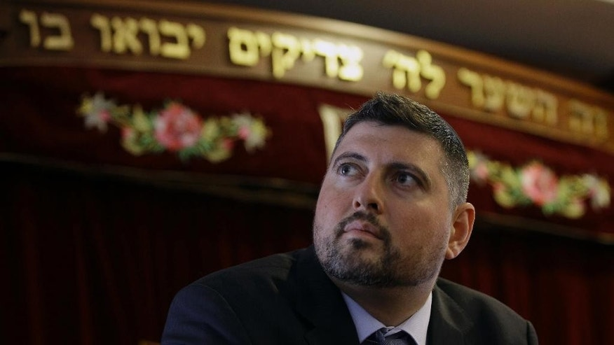 In this picture taken Friday, May 30, 2014, Csanad Szegedi sits in a Budapest Synagogue. Szegedi was a rising star of Hungary's far-right, dumped by his party after he admitted he was a Jew. Two years later, Csanad Szegedi has completed an astonishing transformation: He goes to synagogue, eats Kosher food and has adopted the Hebrew name Dovid. (AP Photo/Peter Kohalmi)