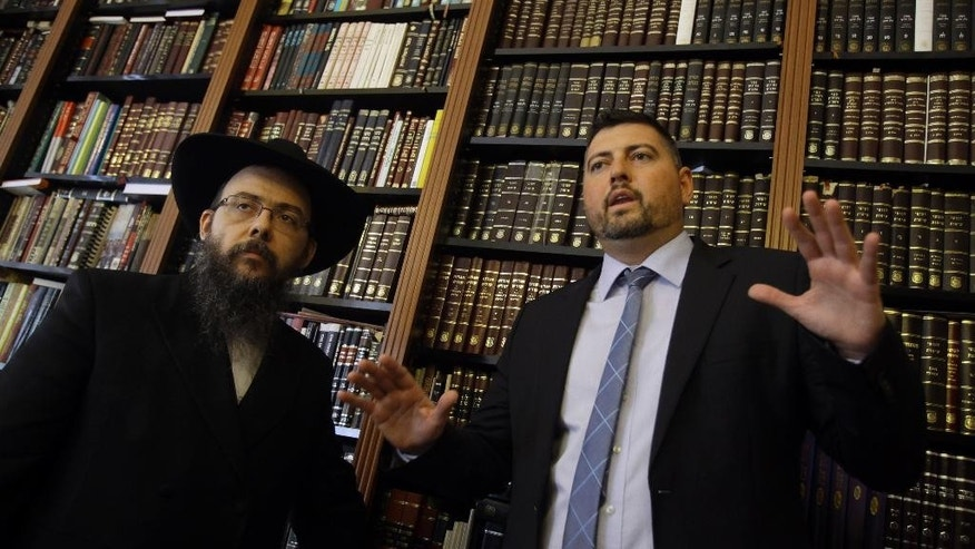 In this picture taken Friday, May 30, 2014, Csanad Szegedi, right, speaks with Chief Chabad Rabbi Boruch Oberlander in Budapest. Szegedi, was a rising star of Hungary's far-right, dumped by his party after he admitted he was a Jew. Two years later, Csanad Szegedi has completed an astonishing transformation: He goes to synagogue, eats Kosher food and has adopted the Hebrew name Dovid. (AP Photo/Peter Kohalmi)
