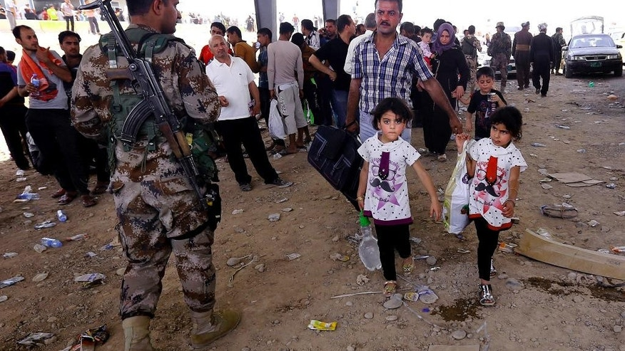 FILE - In this Tuesday, June 10, 2014 file photo, A Kurdish policeman stands guard while refugees from Mosul head to the self-ruled northern Kurdish region in Irbil, Iraq, 350 kilometers (217 miles) north of Baghdad. The Islamic State of Iraq and the Levant, the al-Qaida breakaway group, on Monday and Tuesday took over much of Mosul in Iraq and then swept into the city of Tikrit further south. An estimated half a million residents fled Mosul, the economically important city. (AP Photo, File)
