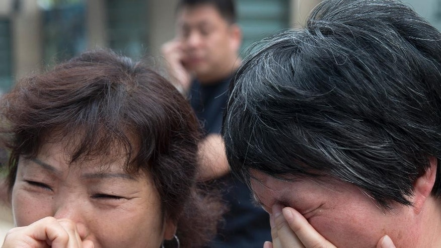 June 11, 2014: Chinese relatives of passengers onboard the missing Malaysia Airlines Flight 370 cry outside the airlines' office after officials from the airline refused to meet with them in Beijing, China. (AP)