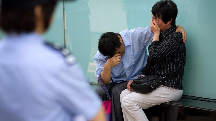 A policewoman watches a couple, whose son was onboard the missing Malaysia Airlines Flight 370, cry after officials from the airlines refused to meet them outside the airlines' office building in Beijing, China Wednesday, June 11, 2014. Despite a massive air and sea search, no trace of Flight 370 has been found, three months after it vanished after taking off from Kuala Lumpur bound for Beijing.  (AP Photo/Andy Wong)