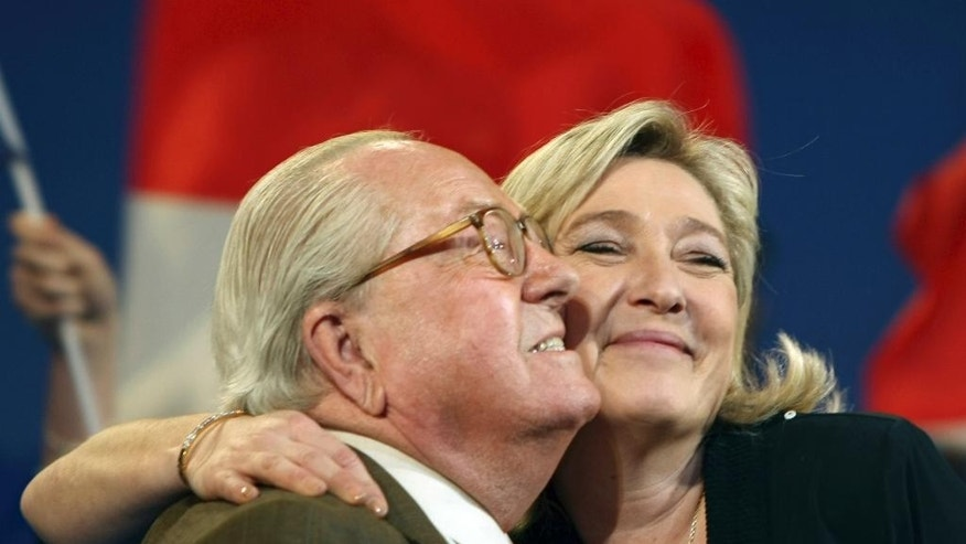 FILE -  This Sunday, March 4, 2012, file photo shows honorary President of  far-right  party National Front Jean-Marie Le Pen, left, and his daughter French far-right leader and National Front Party candidate for the 2012 French presidential elections, Marine Le Pen, during a campaign meeting in Marseille, southern France. A Greek tragedy is playing out in the House of Le Pen, the seat of France's rising far right, with the wounded patriarch lashing out at his daughter, his political heir, in a feud over an anti-Semitic smear that goes to the heart of her efforts broaden the party's support.(AP Photo/Claude Paris)