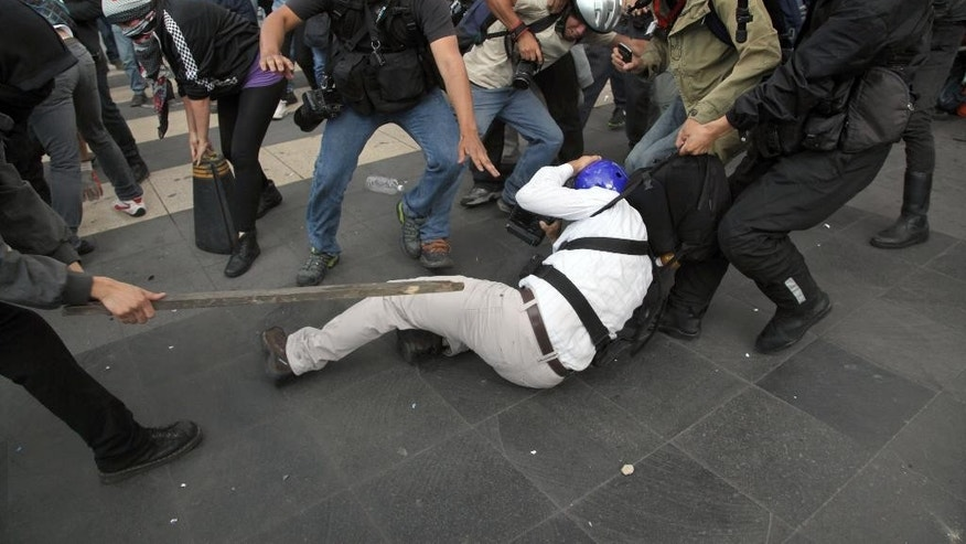 Anarchists, left, attack photojournalist Luis Castillo, center back to the camera, as other photojournalists try rescue him during a march in downtown Mexico City, Tuesday, June 10, 2014. Dozen of anarchists attacked photographers who covered the march of 43th anniversary of the 1971 student massacre known as ''El Halconazo''. (AP Photo/Marco Ugarte))