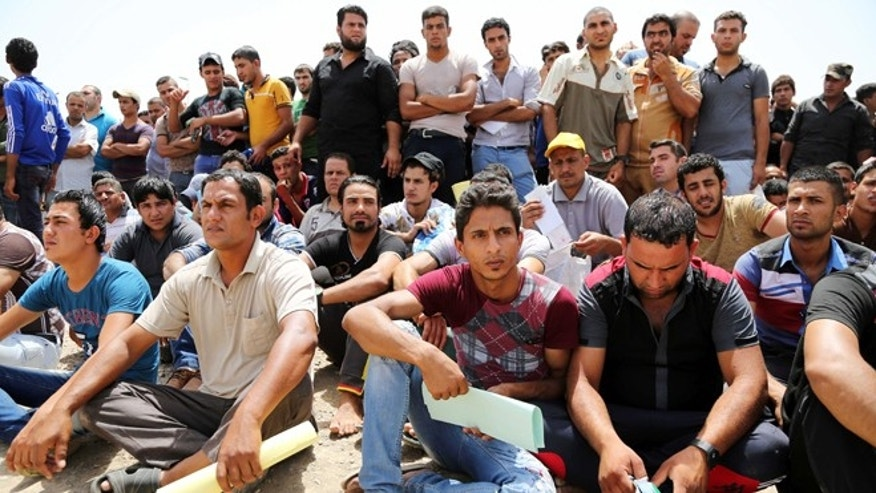 June 12, 2014: Iraqi men gather outside of the main army recruiting center to volunteer for military service in Baghdad, Iraq, after authorities urged Iraqis to help battle insurgents.