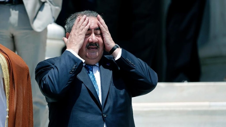 "Iraqi Foreign Minister Hoshyar Zebari reacts to the heat before a group photo during an EU-Arab league Foreign Ministers summit in Athens, on Wednesday, June 11, 2014. The fall of the major northern Iraqi city of Mosul to insurgents must push the country's leaders to work together and deal with the ""mortal threat"" facing Iraq, the country's foreign minister said Wednesday.(AP Photo/Petros Giannakouris)"