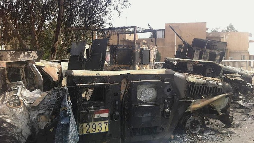 Iraqi army armored vehicles are seen burned on a street of the northern city of Mosul, Iraq, Thursday, June 12, 2014. The al-Qaida-inspired group that captured two key Sunni-dominated cities in Iraq this week vowed on Thursday to march on to Baghdad, raising fears about the Shiite-led government's ability to slow the assault following the insurgents' lightning gains. Fighters from ISIL on Wednesday took Saddam Hussein's hometown of Tikrit, as soldiers and security forces abandoned their posts and yielded ground once controlled by U.S. forces. (AP Photo)