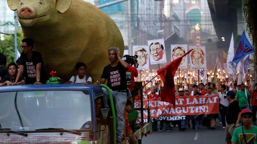 A giant effigy of a pig, leads activists carrying lighted torches, as they march towards the Presidential Palace in Manila to demand that Philippine President Benigno Aquino III prosecute all officials, including some of his allies, who were allegedly involved in stealing from state funds, known as pork barrel funds, which are intended for projects to help the poor Thursday, June 12, 2014 in the Philippines. Three senators and several of their associates have been charged with plunder for allegedly receiving hundreds of millions of pesos (millions of dollars) in kickbacks from a businesswoman who skimmed from the money off government allocations for the poor.(AP Photo/Bullit Marquez)