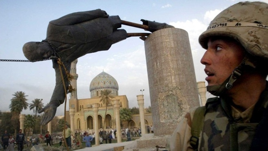 April 9, 2003: In this file photo, U.S. Marine Corp Assaultman Kirk Dalrymple watches as a statue of Iraq's President Saddam Hussein fall in central Baghdad's Firdaus Square