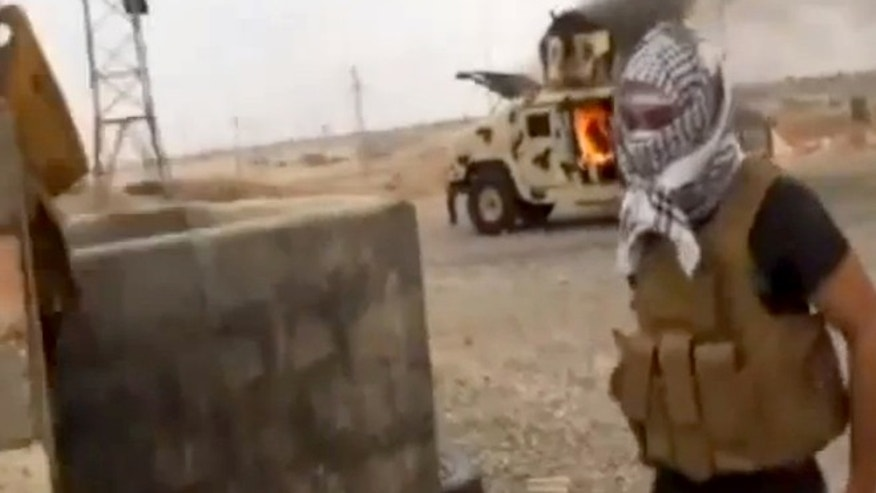 June 11, 2014: This image made from video posted by Iraqi0Revolution, a group supporting the Al Qaeda breakaway Islamic State of Iraq and the Levant, which has been verified and is consistent with other AP reporting, shows a militant standing in front of a burning Iraqi Army Humvee in Tikrit, Iraq.
