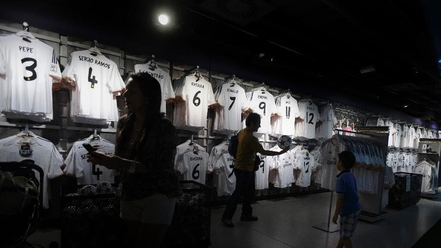 In this picture taken on May 18, 2014, Real Madrid's supporters play with a ball inside the official Real Madrid shop of the Santiago Bernabeu stadium in Madrid, Spain. The European Union is investigating whether government loan guarantees for seven soccer clubs violate EU competition law, designed in part to prevent businesses from enjoying unfair advantage through state intervention. The probe is examining tax breaks granted to the Real Madrid, Barcelona, Athletic Bilbao and Osasuna soccer clubs _ but that's a small part of government assistance to Spain's soccer league, according to the AP review.  (AP Photo/Daniel Ochoa de Olza)