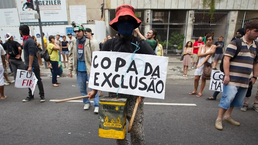 "A demonstrator protests with a sing that reads in Portuguese, "" Cup of exclusion"", during a march against the FIFA 2014 soccer World Cup, at Copacabana beach, Rio de Janeiro, Brazil, Thursday, June 12, 2014. The demonstrators are demanding better public services and protesting the money spent on the soccer tournament. (AP Photo/Leonardo Wen)"